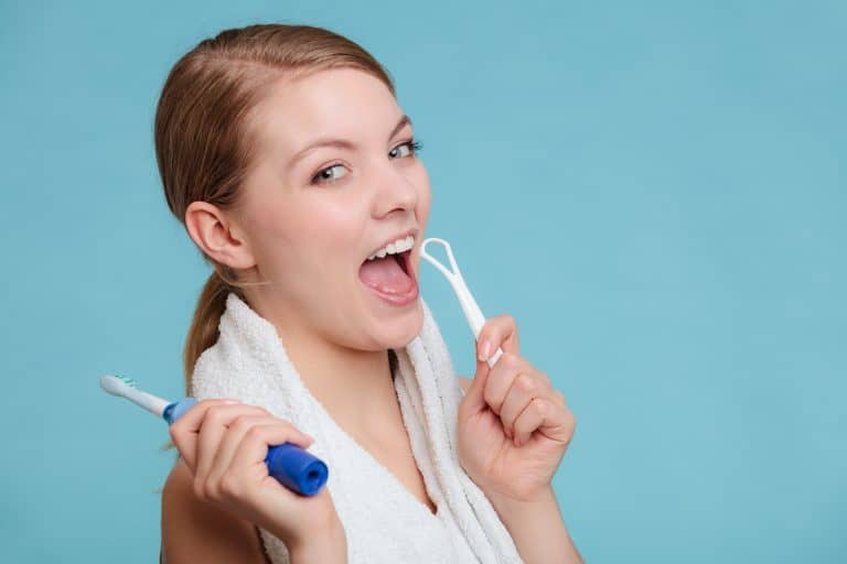 Lady-using-a-tongue-scraper-to-clean-tongue