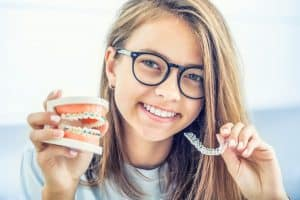 Lady holding a mouthpiece with braces and clear aligners