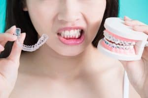 Patient holding invisalign aligners and traditional braces